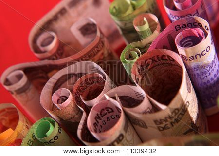 Curled Mexican peso money bills. Background
