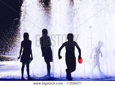 Silhouette of children playing in a fountain