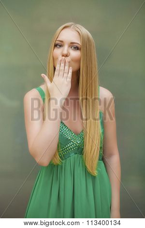 Young blonde woman blowing while sending an air kiss, indoor