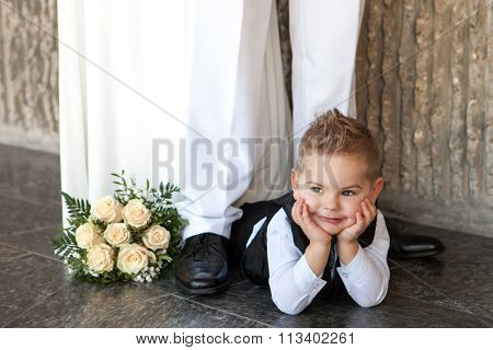 The little thoughtful boy lies on a floor with a bridal bouquet at a wedding