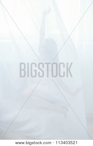 Abstract. Girl Sitting Behind A White Tulle
