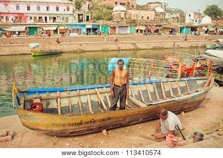 Repairmen Repairing Leaky Fishing Boat On River Banks Of Indian City With Historical Ghats And House