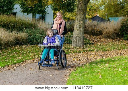 Disability a disabled child in a wheelchair relaxing outside