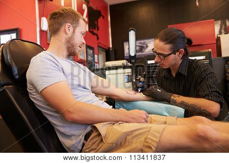Man Sitting In Chair Having Tattoo On Arm In Parlor