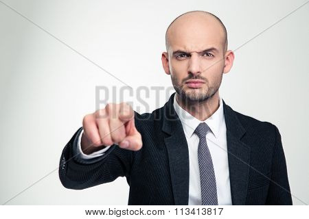Angry handsome businessman in black suit and tie pointing on you over white background