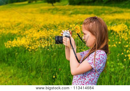 Cute little girl taking pictures with a camera