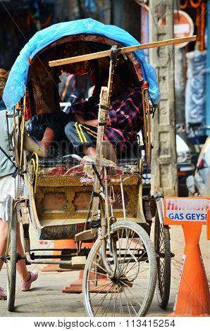 Local sleeping in his rickshaw