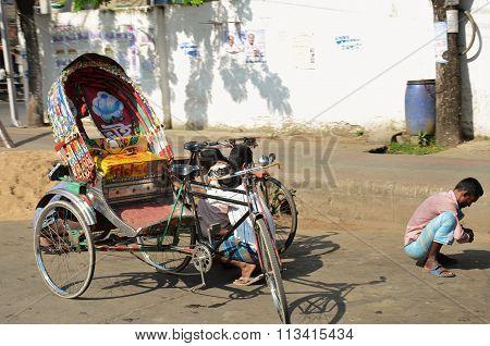 Empty rickshaw, driver squats on the street