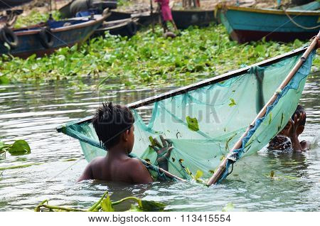 Bangladeshi children in the river with fishing net