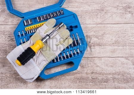 Steel Toolset And Working Glove On A Wooden Table