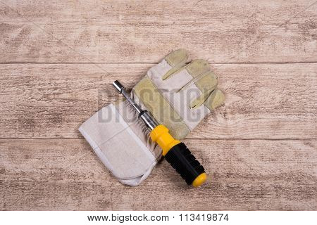 Steel Tool And Working Glove On A Wooden Table