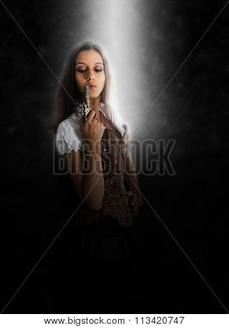Three Quarter Length Portrait of Young Brunette Woman Wearing Old Fashioned Western Themed Costume with Corset Blowing on End of Antique Pistol, Lit by Spotlight in Dark Studio with Copy Space