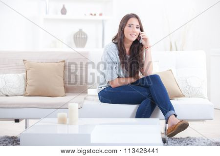 Woman making a call whilst on her sofa