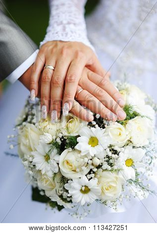 Hands Of The Groom And The Bride With Wedding Rings And A Wedding Bouquet From Roses