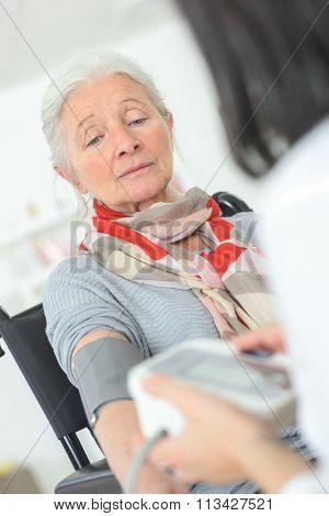 Having her blood pressure taken