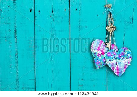 Key and hearts hanging on rustic door