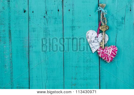Key and hearts hanging on old painted wood door