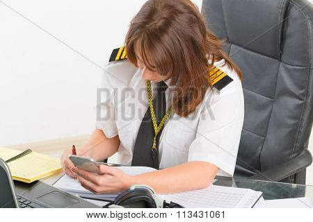 Beautiful woman pilot wearing uniform with epaulettes using mobile phone and laptop at preflight briefing