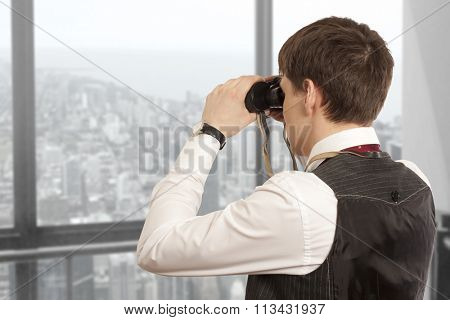Business concept. Businessman looks through a binoculars