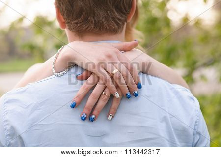Loving Young Woman Stands With Her Arms Around His Neck, View Over His Shoulder Of Her Face