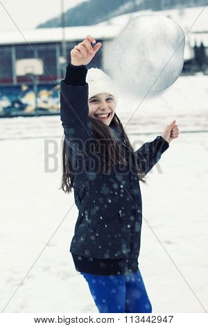 Young Smiling Girl Throwing Snow Ball