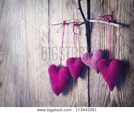 Crochet Pink Hearts On Wooden Background.