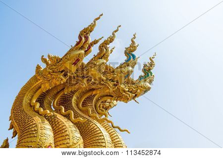 serpent king or king of naga statue in thai temple on blue sky background