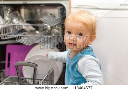 Little Boy Putting Dishes Into The Dishwasher