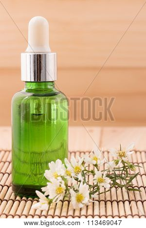 Bottle Serum For Beauty Spa And Therapy Treatment Wiht Wildflowers  On Wooden Background.