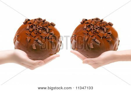 Two hands with a chocolate pie are stretched towards