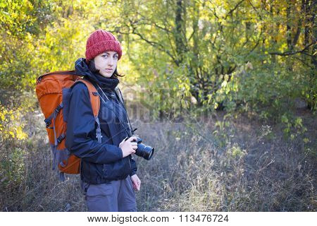 A Girl With A Camera And A Backpack