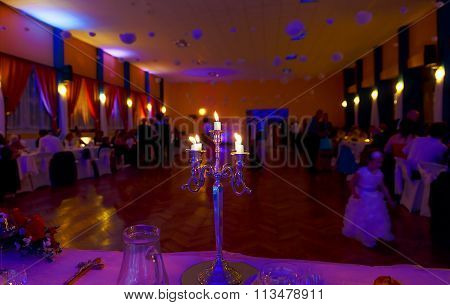 silver chandelier and burning candles on decorated wedding table.