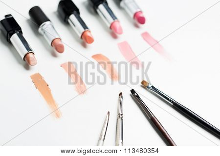 close up of lipsticks range with makeup brushes