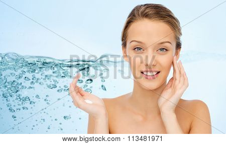smiling young woman applying cream to her face