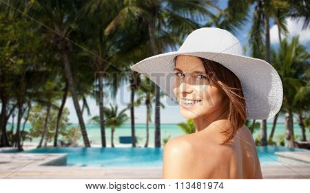 happy young woman in sunhat over hotel beach