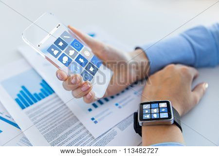 close up of hands with smart phone and watch icons