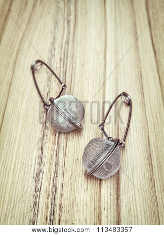 Two Tea Strainers On The Wooden Background