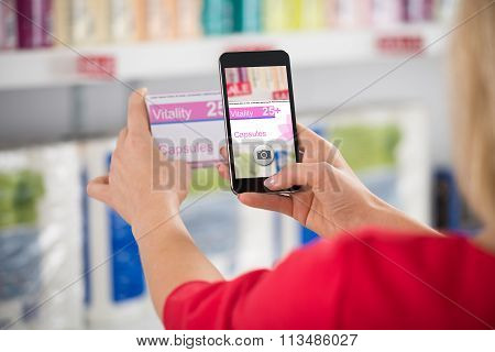 Woman Photographing Capsule Packet In Store