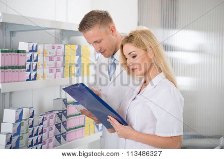 Smiling Pharmacists Checking Inventory At Pharmacy