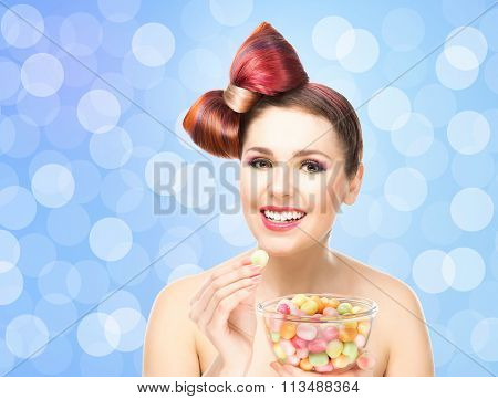 Beautiful smiling girl eating sweets from a bowl on blink background.