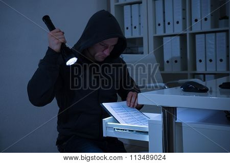 Robber With Flashlight Searching For Documents In Office