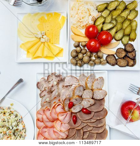 Cutting Sausages, Pickles And Salads On A Banquet Table
