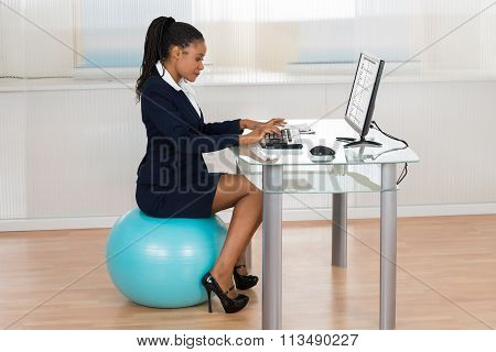 Businesswoman Sitting On Fitness Ball Using Computer