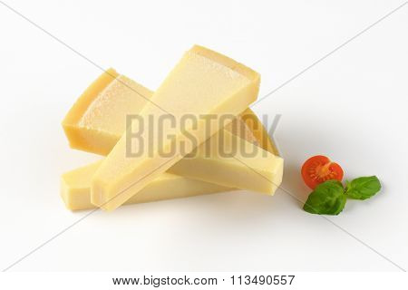three wedges of fresh parmesan cheese on white background