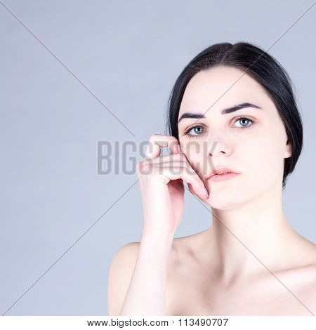 Woman with black hair gray eyes and smooth face touching her cheek
