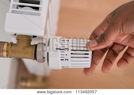 Person's Hand Adjusting Radiator Temperature