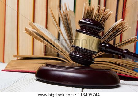 Law concept - Open law book with a wooden judges gavel on table