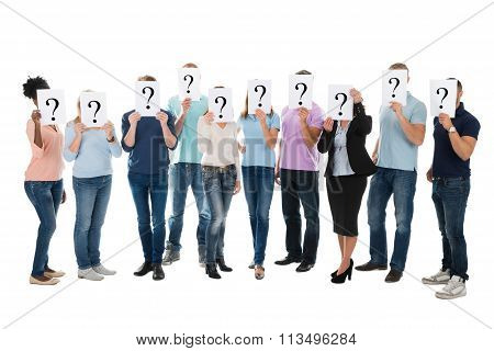 Creative Business Team Hiding Faces With Question Mark Signs