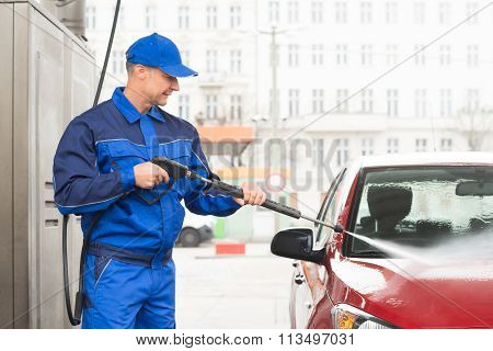 Serviceman With High Pressure Water Jet Washing Car