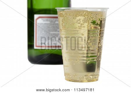 Champagne In Disposable Cup On The Background Blurred Bottle Of Champagne